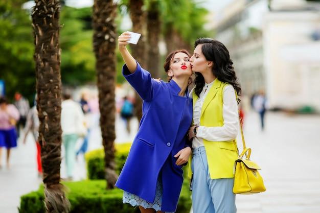 Twee vriendinnen nemen selfie op straat met palmbomen op herfstvakantie.
