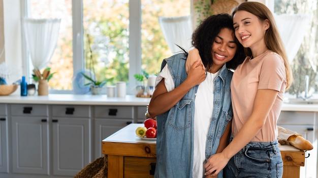 Twee vriendinnen omarmd in de keuken met kopie ruimte