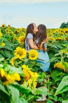 Twee vriendinnen omhelzen elkaar op zonnebloemveld