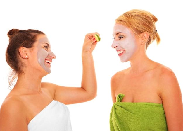 Twee vriendinnen ontspannen met gezichtsmaskers op over wit