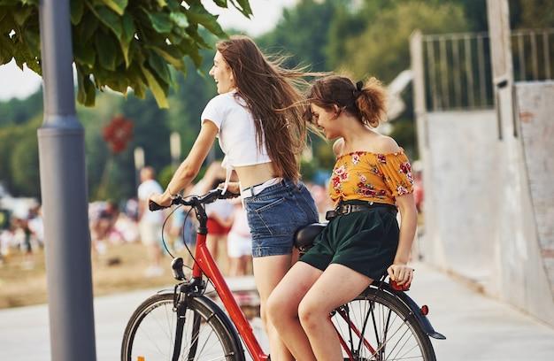 Twee vriendinnen op de fiets hebben plezier in het park in de buurt van oprit.