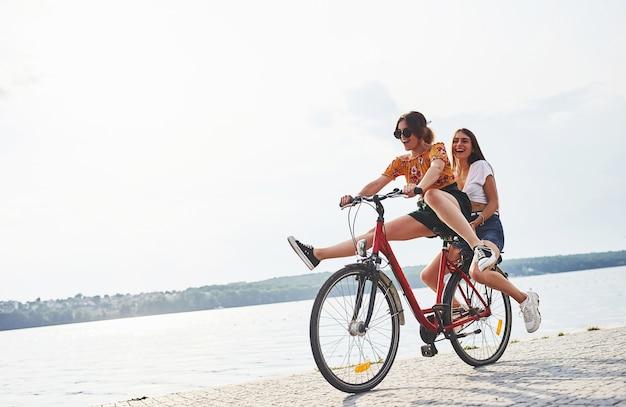 Twee vriendinnen op de fiets hebben plezier op het strand bij het meer.