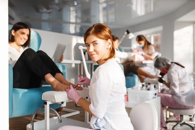 Twee vriendinnen, pedicureproces in de schoonheidssalon. professionele schoonheidsspecialisten en vrouwelijke klanten