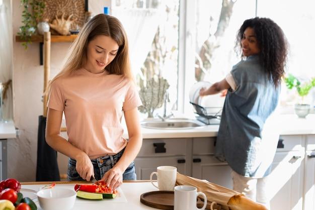 Twee vriendinnen plezier tijdens het samen koken