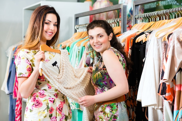 Twee vriendinnen plezier tijdens het winkelen in de boetiek of winkel mode