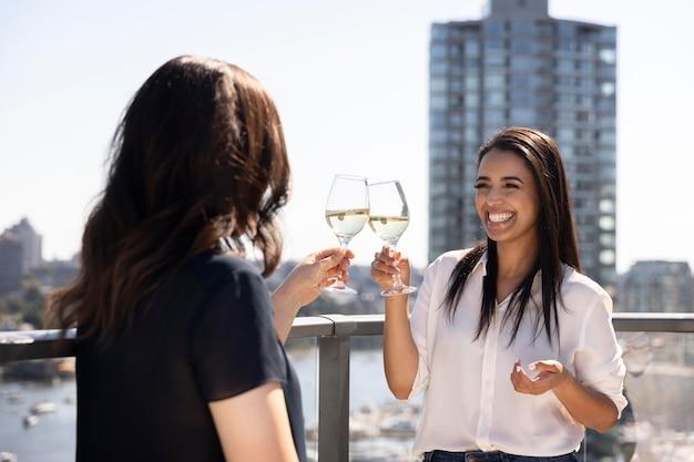Twee vriendinnen praten en genieten van wat wijn op een dakterras