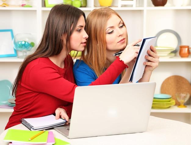 Twee vriendinnen praten en studeren in de keuken