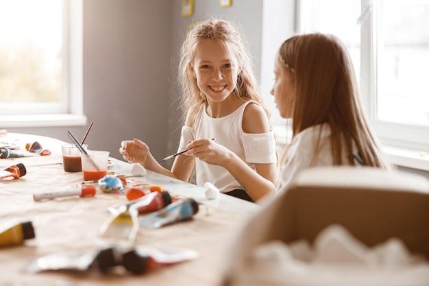 Twee vriendinnen praten tijdens het schilderen met aquarellen op school