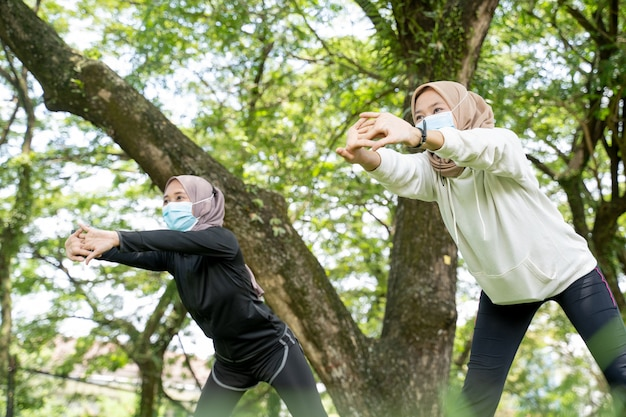 Twee vriendinnen van moslimvrouwen oefenen samen en dragen een masker voor bescherming tegen virussen