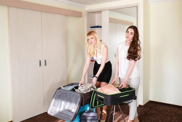 Twee vriendinnen verzamelen een koffer in een hotelkamer