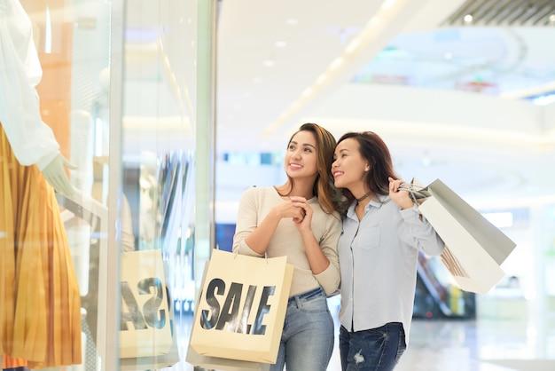 Twee vriendinnen windowshopping in het winkelcentrum te koop