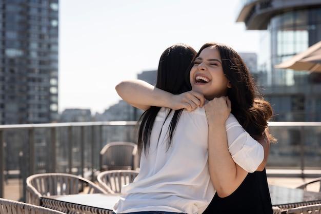 Twee vriendinnen zien elkaar op een dakterras en knuffelen