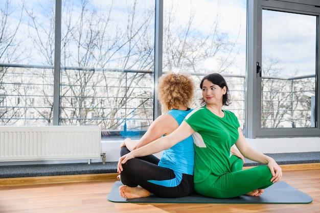 Twee vriendinnen zitten in lotus yoga houding rug aan rug, groepsoefening training binnenshuis