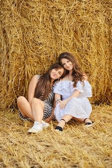 Twee vriendinnen zitten leunend tegen een stapel op een veld