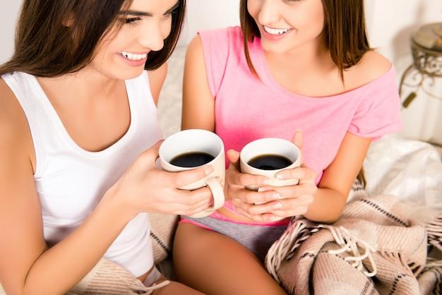 Twee vrij gelukkige meisjes die in de ochtend koffie drinken