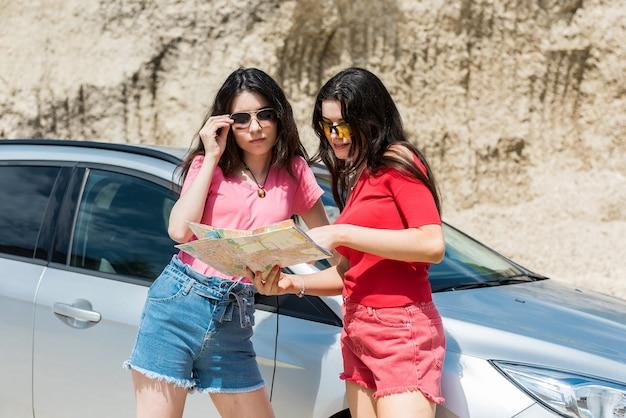 Twee vrij kaukasische vrouwelijke bestuurder die een kaart dichtbij auto leest
