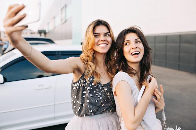 Twee vrij modieuze meisjes selfie-portret maken op parking.