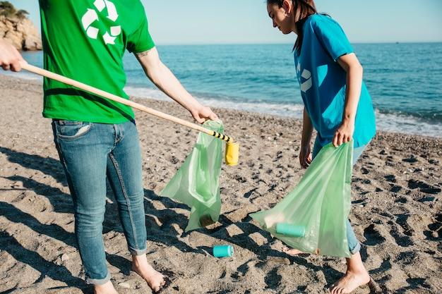 Twee vrijwilligers die afval verzamelen op het strand