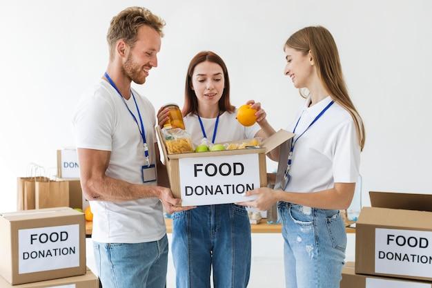 Twee vrijwilligers houden een voedseldonatiebox vast terwijl een ander hem vult