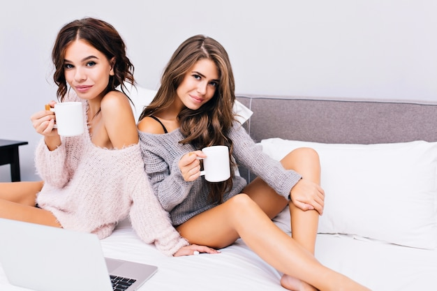 Twee vrolijke aantrekkelijke meisjes koelen op bed in een modern appartement. mooie modieuze modellen in gebreide truien, blote lange benen, genietend van koffie. ontspan tijd, goedemorgen, lachend, vrolijk.