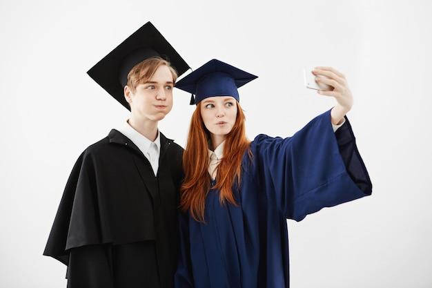 Twee vrolijke afgestudeerden van de universiteit gek maken selfie.