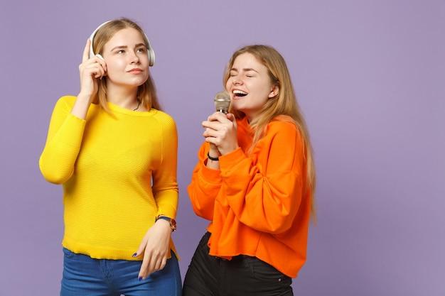 Twee vrolijke blonde tweelingzusters meisjes in levendige kleding luisteren muziek met koptelefoon, zingen lied in microfoon geïsoleerd op violet blauwe muur. mensen familie levensstijl concept.