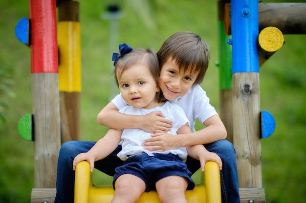Twee vrolijke broers en zussen, broer die zijn zus knuffelt en spelen in een park met houten spellen in een vrije en natuurlijke ruimte.