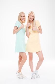 Twee vrolijke dames maken een cool gebaar dat over een witte muur wordt geïsoleerd.