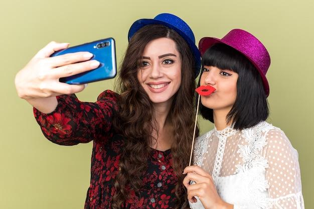 Twee vrolijke en zelfverzekerde jonge feestmeisjes die een feestmuts dragen, de een houdt valse lippen op een stok voor de lippen en de ander glimlacht en neemt selfie samen geïsoleerd op de olijfgroene muur