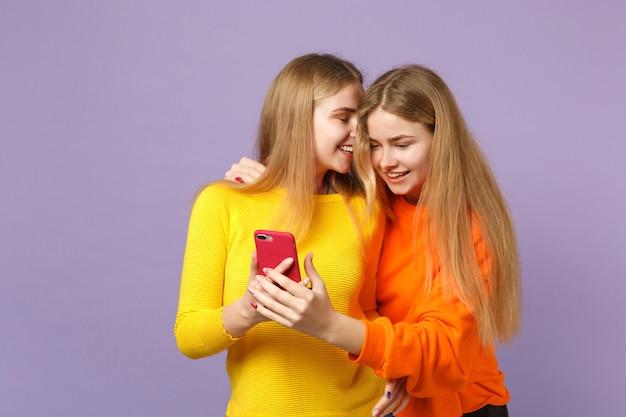 Twee vrolijke jonge blonde tweelingzusters meisjes in levendige kleding met behulp van mobiele telefoon, sms-bericht typen geïsoleerd op pastel violet blauwe muur. mensen familie levensstijl concept.