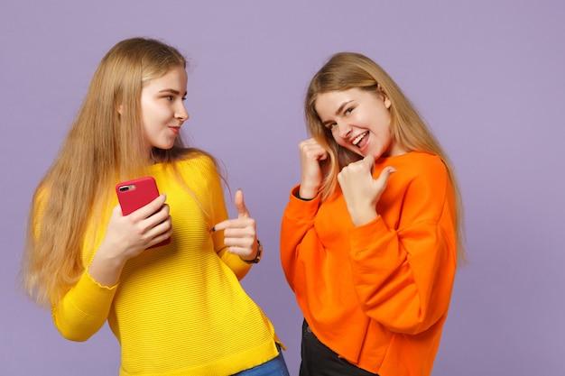 Twee vrolijke jonge blonde tweelingzusters meisjes in levendige kleren wijzend met de duim opzij met mobiele telefoon geïsoleerd op pastel violet blauwe muur. mensen familie levensstijl concept.