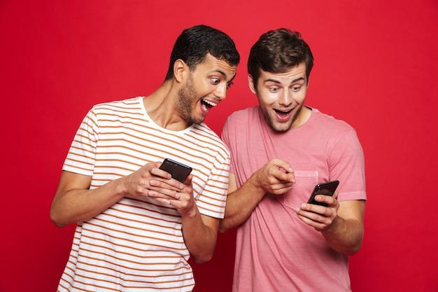 Twee vrolijke jonge mannen die zich geïsoleerd over rode muur bevinden, spelen op mobiele telefoon