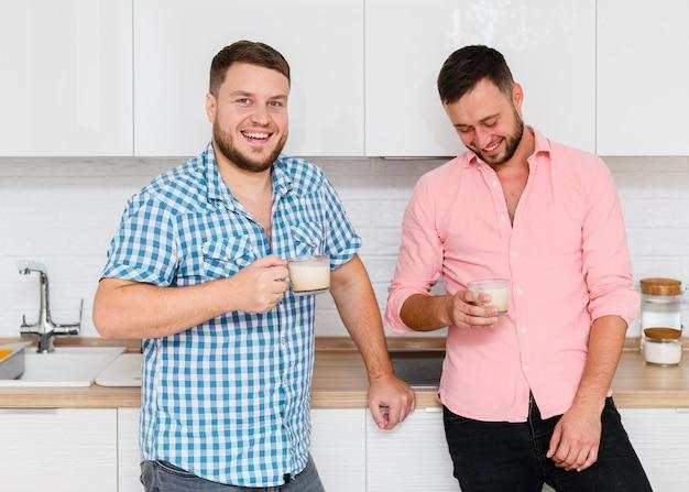Twee vrolijke jonge mannen met koffie in de keuken