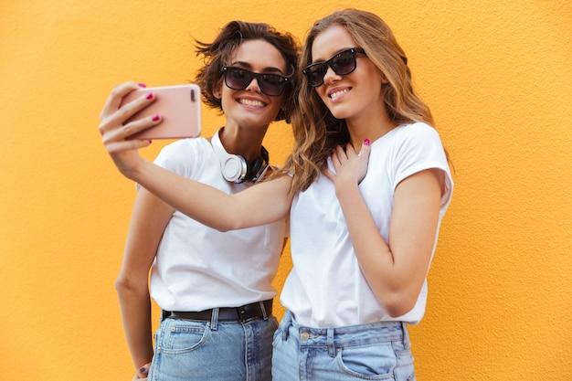 Twee vrolijke jonge tienermeisjes in zonnebril nemen een selfie