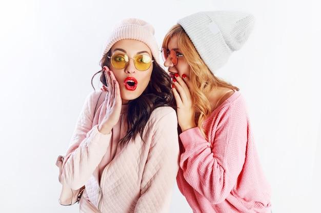 Twee vrolijke jonge vrienden in perfecte stemming met tijd samen op wit isoleren achtergrond. positieve meisjes met roze knusse truien en pullover, trendy hoed, schattige bril.
