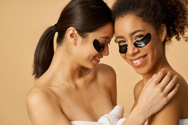 Twee vrolijke jonge vrouwen gewikkeld in een handdoek poseren met aangebrachte zwarte hydrogel onder het oog