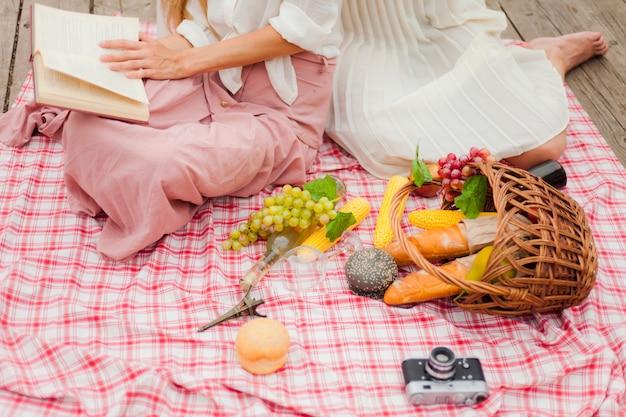 Twee vrolijke jonge vrouwen hebben een picknick buiten op een zomerse dag.