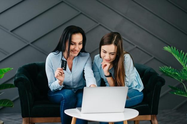 Twee vrolijke jonge vrouwen kijken naar laptopscherm tijdens het winkelen in online winkels