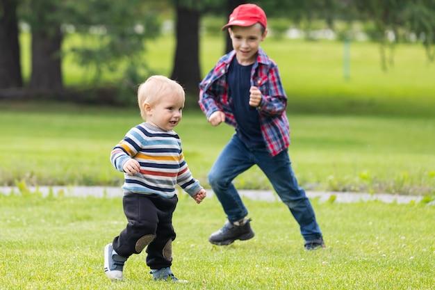 Twee vrolijke jongensbroers van verschillende leeftijden spelen plezier, rennen over het groene veld op een warme zomerdag.
