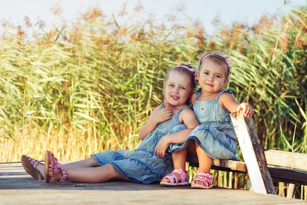 Twee vrolijke kaukasische meisjes in zomer park.