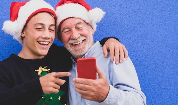 Twee vrolijke kerstmannen die elkaar omhelzen tegen een blauwe muur, een grootvader met zijn tienerkleinzoon, lachen terwijl ze samen naar de mobiele telefoon kijken. concept van moderne en technologische familie