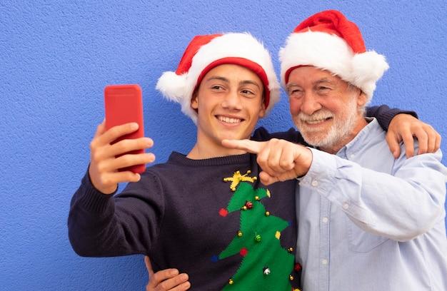 Twee vrolijke kerstmannen knuffelen elkaar tegen een blauwe muur, een grootvader met zijn tienerkleinzoon, glimlachen terwijl ze een selfie maken met een smartphone. concept van moderne en technologische familie