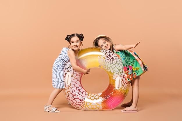 Twee vrolijke kleine meisjes in stranduitrusting met zwemring in studio