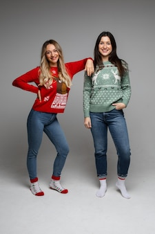 Twee vrolijke langharige vriendinnen blonde en brunette dragen warme winter truien poseren op grijze studio