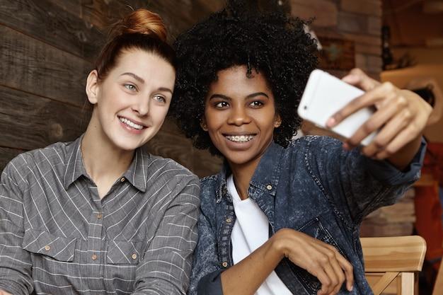 Twee vrolijke lesbiennes van verschillende rassen met plezier binnenshuis