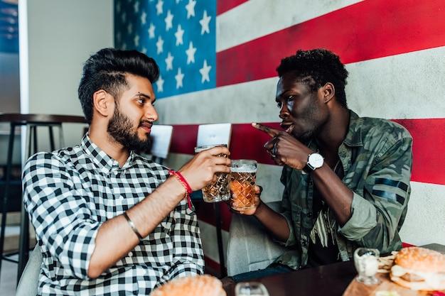 Twee vrolijke man die plezier heeft terwijl hij tijd doorbrengt met vrienden in een pub en bier drinkt.