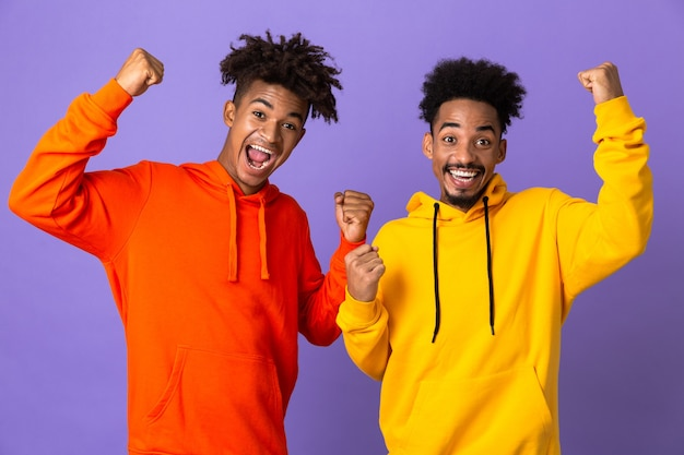 Twee vrolijke mannelijke vrienden in kleurrijke hoodies
