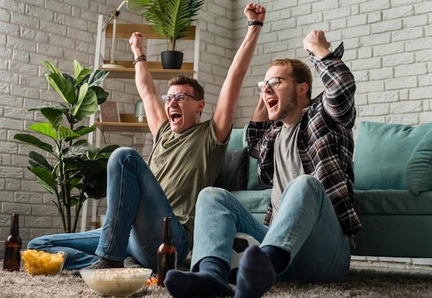 Twee vrolijke mannelijke vrienden kijken samen naar sport op tv terwijl ze snacks en bier hebben