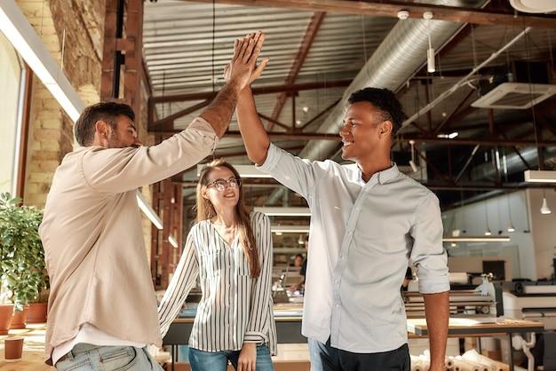 Twee vrolijke mannen die highfive geven terwijl ze met collega's in het moderne kantoorteamwerk staan