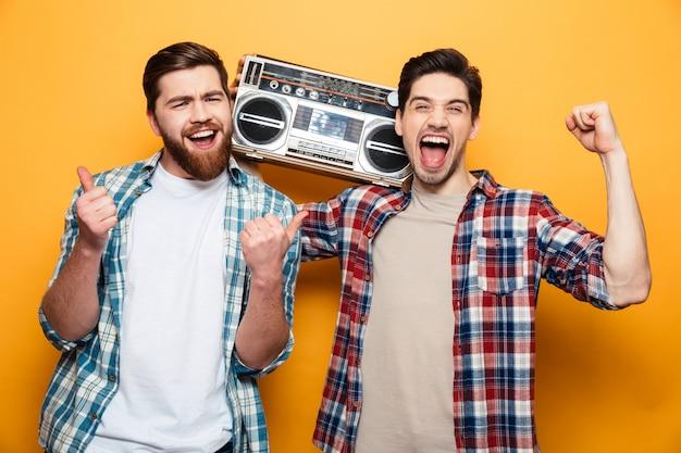 Twee vrolijke mannen in shirts luisteren muziek van platenspeler en geniet over gele muur